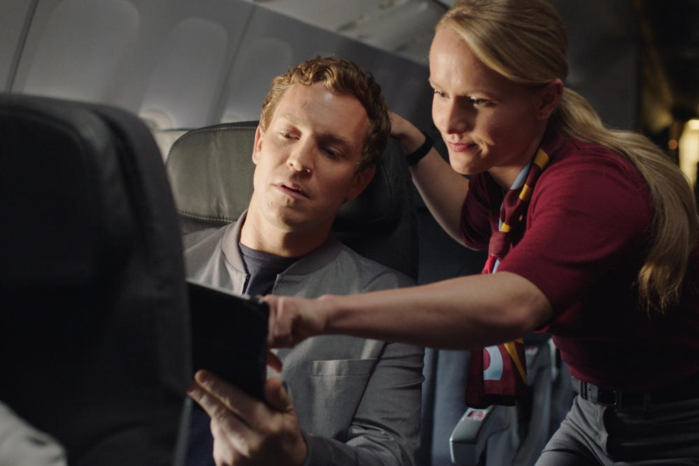 A couple sitting in Rouge seating using the in-flight system player aboard an Air Canada Rouge flight.